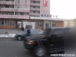 North Korea police officer issuing a speeding ticket. Hummer H2 in the foreground.